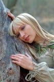 Middeleeuwse vrouw die op boomstam ligt Stock Afbeelding