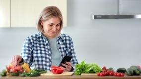 Middelgroot close-up die jong veganistmeisje charmeren die verse groenten eten die gebruikend smartphone babbelen stock videobeelden