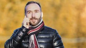 Middelgroot close-upportret van de glimlachende aantrekkelijke mens die gebruikend smartphone spreken stock footage