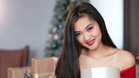 Middelgroot close-upportret van de nieuwsgierige jonge Aziatische vrouw het openen doos van de Kerstmisgift en het glimlachen