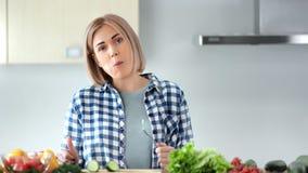 Middelgroot close-upportret van het charmeren van vrouw die smakelijke verse groenten eten die camera bekijken stock video