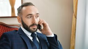 Middelgroot close-upportret van het glimlachen het Kaukasische mannelijke zakenman spreken gebruikend smartphone stock videobeelden