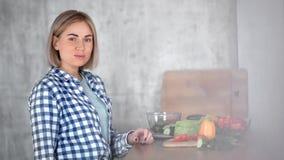 Middelgroot close-upportret van mooie jonge veganistvrouw die groenten eten tijdens kokende maaltijd stock videobeelden
