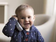 Middelgroot horizontaal schot van eerlijk glimlachend peutermeisje die een stuk speelgoed telefoonontvanger houden aan haar oor royalty-vrije stock afbeeldingen
