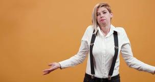 Middelgroot portret van een blondevrouw die verward en uitgespreid haar wapens zijn stock video