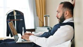 Middelgroot snak geschotene jonge mannelijke zakenmanzitting in hotelbed gebruikend laptop het doorbladeren Web stock footage