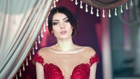 Middelgrote close-up aanbiddelijke Spaanse jonge sexy vrouw in sparkly het gelijk maken van rode kleding stock footage