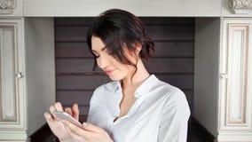 Middelgrote close-up informele jonge vrouw die gebruikend smartphone bij luxe binnenlandse achtergrond glimlacht stock videobeelden