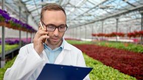 Middelgrote close-up mannelijke landbouwingenieur die het analyseren van het spreken maken gebruikend smartphone stock footage