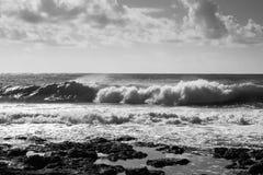 Middelgrote golven die op de rotsen, grijze hemel met wolken verpletteren Stock Foto's