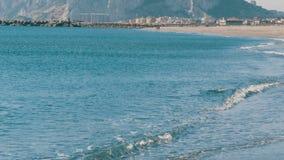 Middellandse Zee in zijn mooie golven, die tegen wit zand en de Rots van Gibraltar tegen achtergrond slaan stock videobeelden