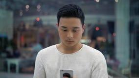 Midden dat van Aziatisch mannetje wordt geschoten die met een telefoon op venstersachtergrond lopen stock videobeelden