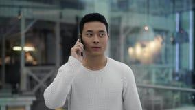 Midden dat van Aziatisch mannetje wordt geschoten die op telefoon spreken terwijl het lopen stock videobeelden