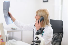 Midden leeftijd artsenvrouw het spreken telefoon royalty-vrije stock foto's