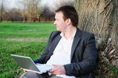 Midden leeftijdsmens met laptop in openlucht Stock Afbeelding