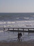 Midden leeftijdspaar dat op strand wandelt stock afbeeldingen