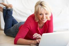 Midden leeftijdsvrouw op haar laptop computer Stock Foto