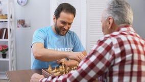 Midden oud mannelijk vrijwilligers het spelen schaak met bejaarde in verpleeghuis, hobby stock footage