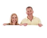 Midden oud paar dat zich achter een leeg wit bevindt Stock Foto