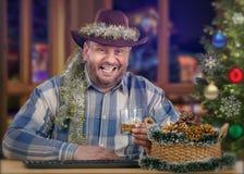 Midden oude cowboy die van whisky op Kerstavond genieten Royalty-vrije Stock Afbeeldingen