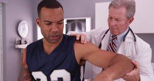 Midden oude mannelijke arts die jonge mannelijke volwassen atleet i behandelen stock afbeeldingen