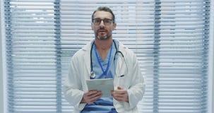 Midden oude mannelijke arts gebruikend tablet en sprekend aan camera 4k stock videobeelden
