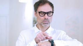 Midden oude mens die smartwatch, online doorbladerend op het werk gebruiken stock videobeelden
