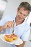 Midden Oude Mens die Verse Grapefruit eet stock foto's