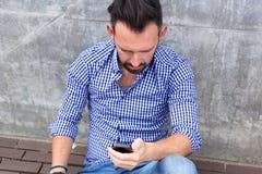 Midden oude mensenzitting die buiten en mobiele telefoon met behulp van Royalty-vrije Stock Afbeelding