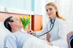 Midden oude patiënt op bed liggen en arts die hem onderzoeken met stethoscoop Royalty-vrije Stock Afbeelding