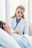 Midden oude patiënt op bed liggen en arts die hem onderzoeken met stethoscoop Royalty-vrije Stock Foto