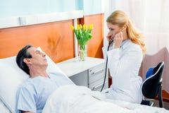 Midden oude patiënt op bed liggen en arts die hem onderzoeken met stethoscoop Stock Afbeelding