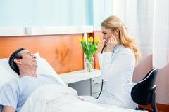 Midden oude patiënt op bed liggen en arts die hem onderzoeken met stethoscoop Royalty-vrije Stock Afbeeldingen