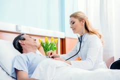 Midden oude patiënt op bed liggen en arts die hem onderzoeken met stethoscoop Stock Afbeeldingen