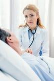 Midden oude patiënt op bed liggen en arts die hem onderzoeken met stethoscoop Royalty-vrije Stock Fotografie
