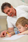Midden oude vader die jonge zoon met thuiswerk helpt Stock Foto