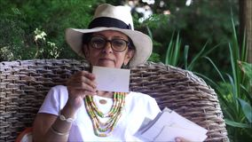 Midden oude vrouw die oude foto's de portiek van de binnenplaatstuin bekijken stock videobeelden
