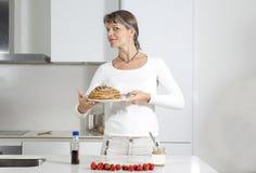 Midden oude vrouw die panckaes met een stapel van pannekoeken maken royalty-vrije stock afbeelding