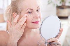 Midden oude vrouw die rimpels in spiegel bekijken Plastische chirurgie en collageeninjecties makeup Macrogezicht selectief stock fotografie