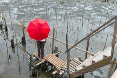 Midden oude vrouw die zich op een bamboebrug, onder een rode umbre bevinden Royalty-vrije Stock Afbeelding