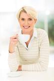 Midden oude vrouw het drinken koffie Stock Afbeelding