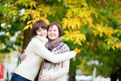 Midden oude vrouw met dochter op een dalingsdag Stock Afbeeldingen