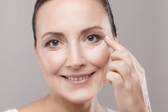 Midden oude vrouw met perfecte gezichtshuid die kosmetische room op huid toepassen dichtbij ogen en camera met toothy glimlach be royalty-vrije stock fotografie