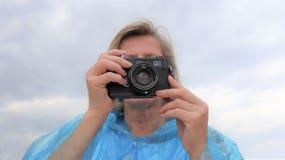 Midden oude vrouwelijke fotograaf die foto's in openlucht nemen stock foto