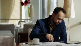 Midden oude zakenman die tablet en grafiek in koffiewinkel gebruiken stock video