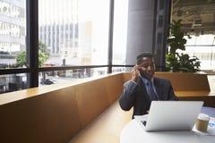 Midden oude zwarte zakenman die telefoon in een modern bureau met behulp van royalty-vrije stock foto