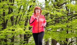 Middenleeftijd die womn sportkleding draagt en in bos loopt stock fotografie