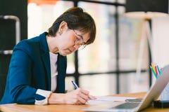 Middenleeftijds Aziatische vrouw die aan administratie in modern bureau, met laptop computer werken Bedrijfseigenaar of onderneme stock foto's