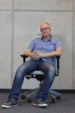 Middenleeftijds balding mens met positie van de oogglazen de slechte zitting inzake stoel in bureau Royalty-vrije Stock Foto