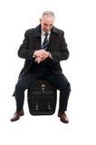 Middenleeftijds bedrijfsmens die tijdzitting controleren op bagage Royalty-vrije Stock Foto's